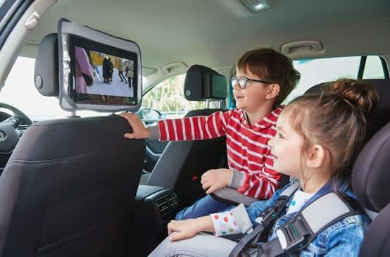 Kinder vor Tablets in Kopfstützen im Auto