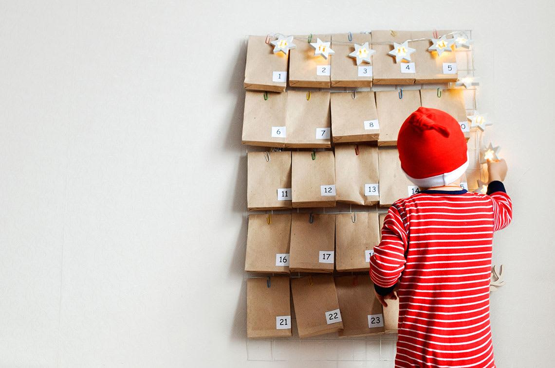 Kind öffnet gebastelten Adventskalender