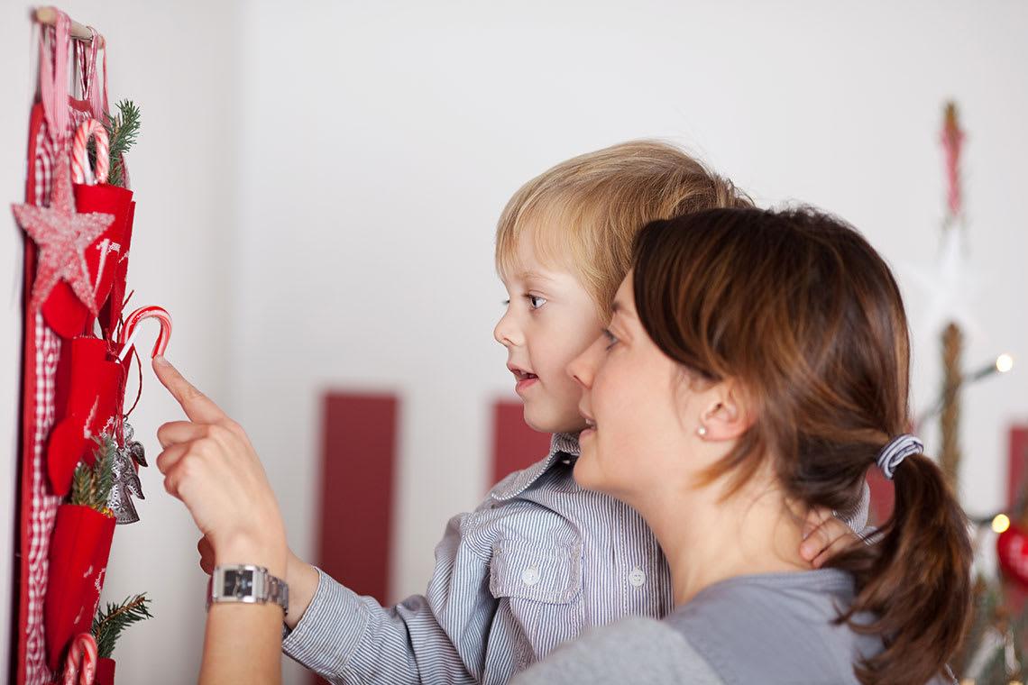 Kind öffnet mit Mutter Adventskalender-Türchen
