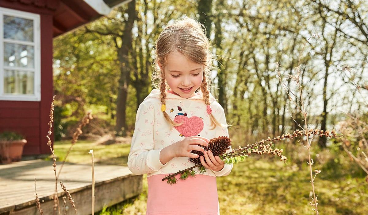 Kind sammelt Tannenzapfen zum Basteln