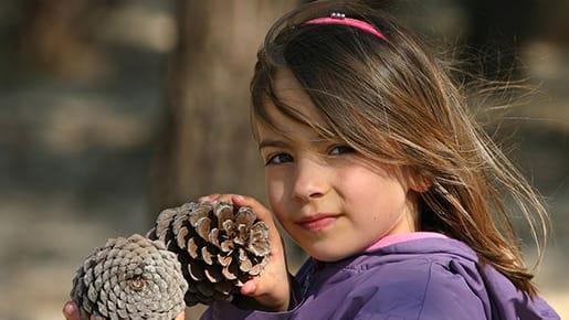 Kind mit Tannenzapfen