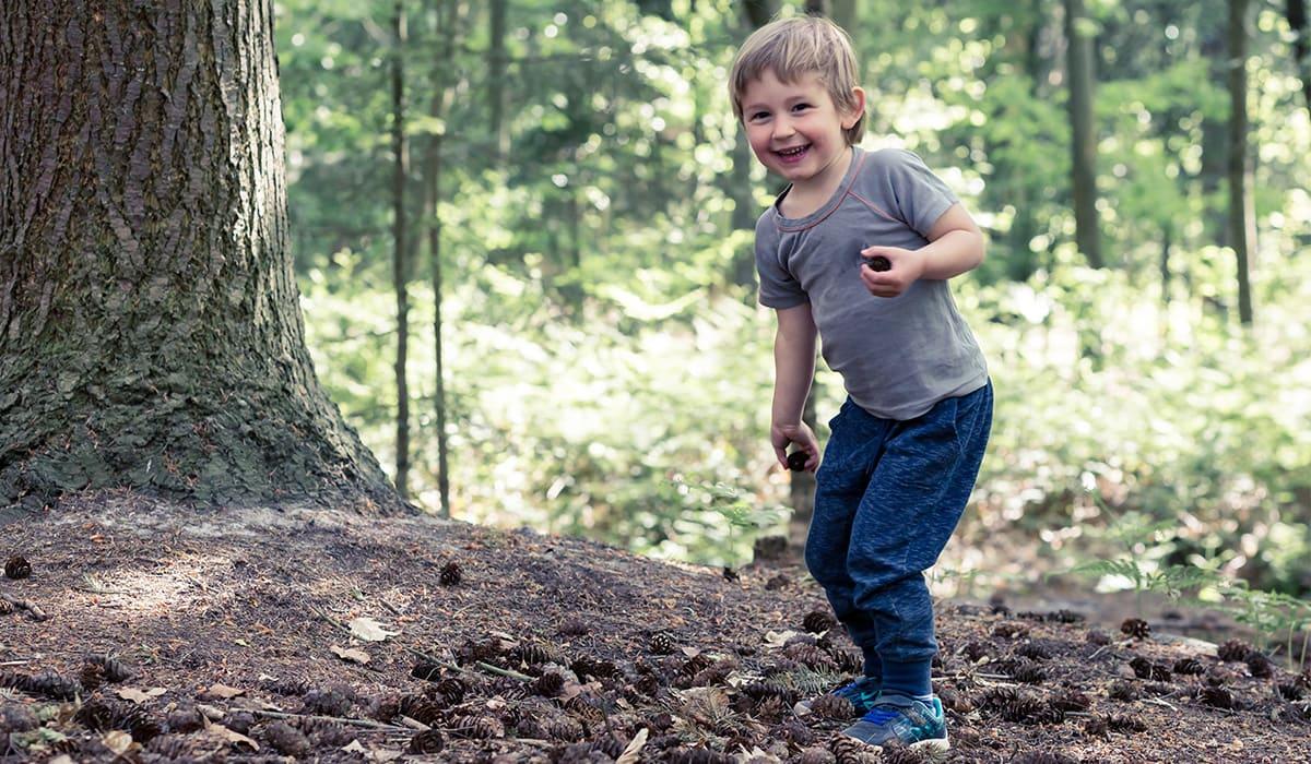 Fröhliches Kind mit vielen Tannenzapfen auf dem Waldboden