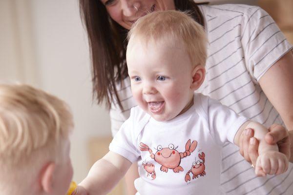 Familie lernt Baby das Laufen