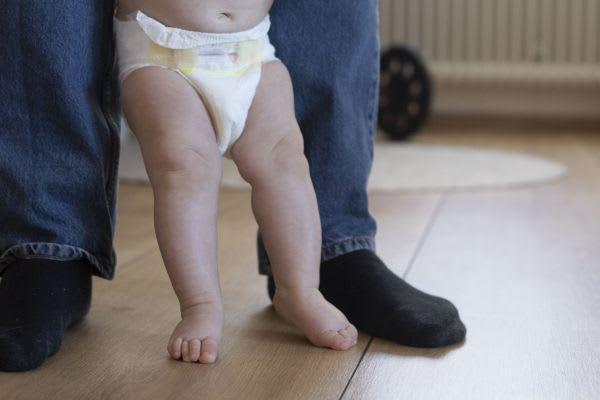 Vater lernt mit seinem Baby das Laufen