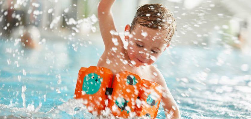 Schwimmen lernen: Junge mit Schwimmgürtel