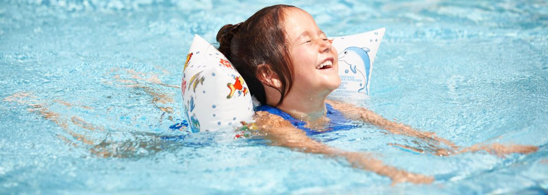 Schwimmen lernen: Mädchen mit Schwimmflügeln