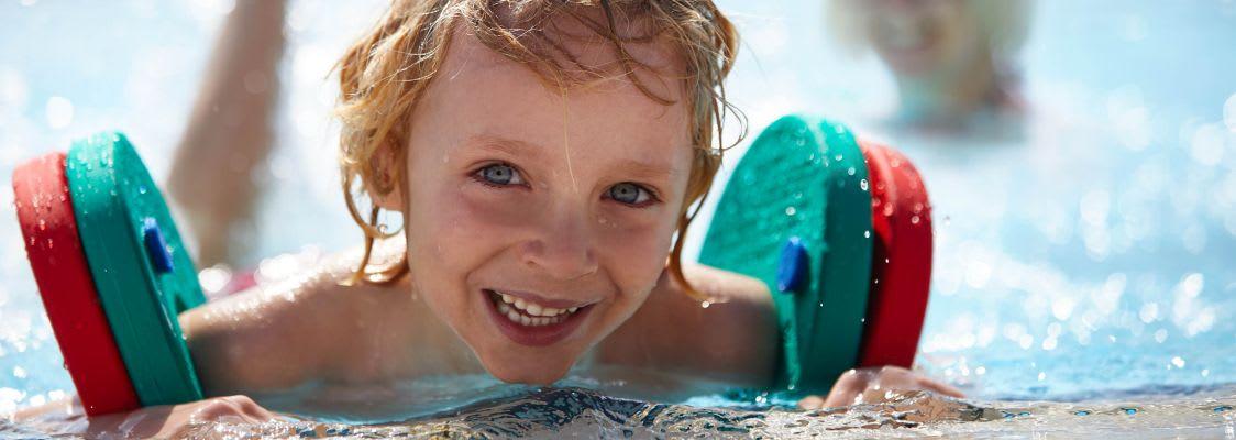 Kind mit Schwimmflügeln im Wasser