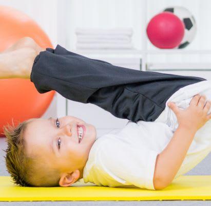 Sportübungen für Kinder: Junge turnt auf Gymnastikmatte