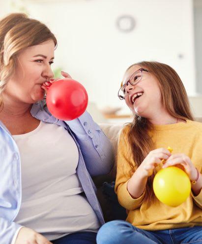 Sportübungen für Kinder: Mutter und Tochter machen Ballonspiele