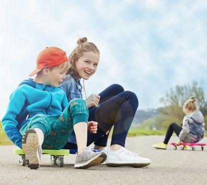 Sportübungen für Kinder: Geschwister spielen mit Rollbrettern