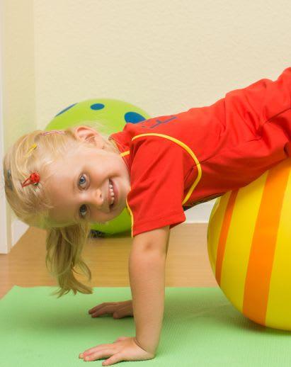 Sportübungen für Kinder: Mädchen turnt mit Gymnastikball