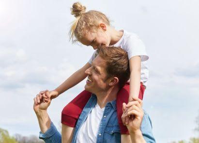 Sportübungen für Kinder: Vater und Tochter spielen draußen