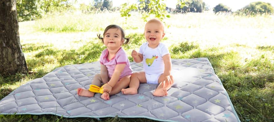 Babys im Sommer anziehen: Babys auf einer Krabbeldecke im Schatten