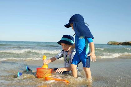 Babys im Sommer anziehen: Babys in UV-Kleidung spielen am Strand