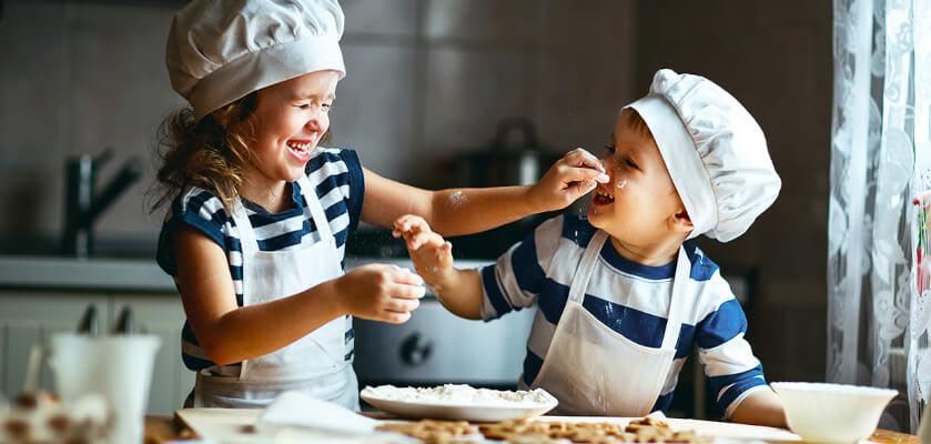 Backen mit Kindern: Geschwister mit lustigen Kochmützen