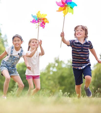 Bastelideen für den Sommer: Kinder spielen mit Windrädern