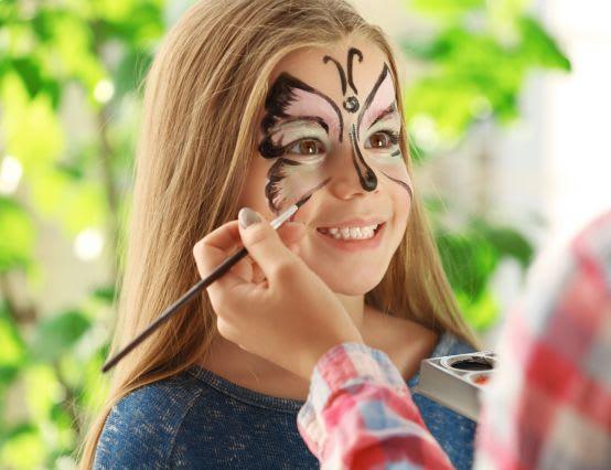 Mädchen bekommt schönen Schmetterling geschminkt