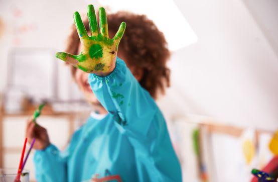 Basteln im Frühling: Kind malt mit Fingerfarben