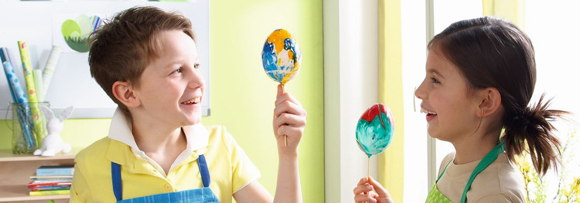 Ostereier färben: Kinder bemalen Eier am Holzspieß