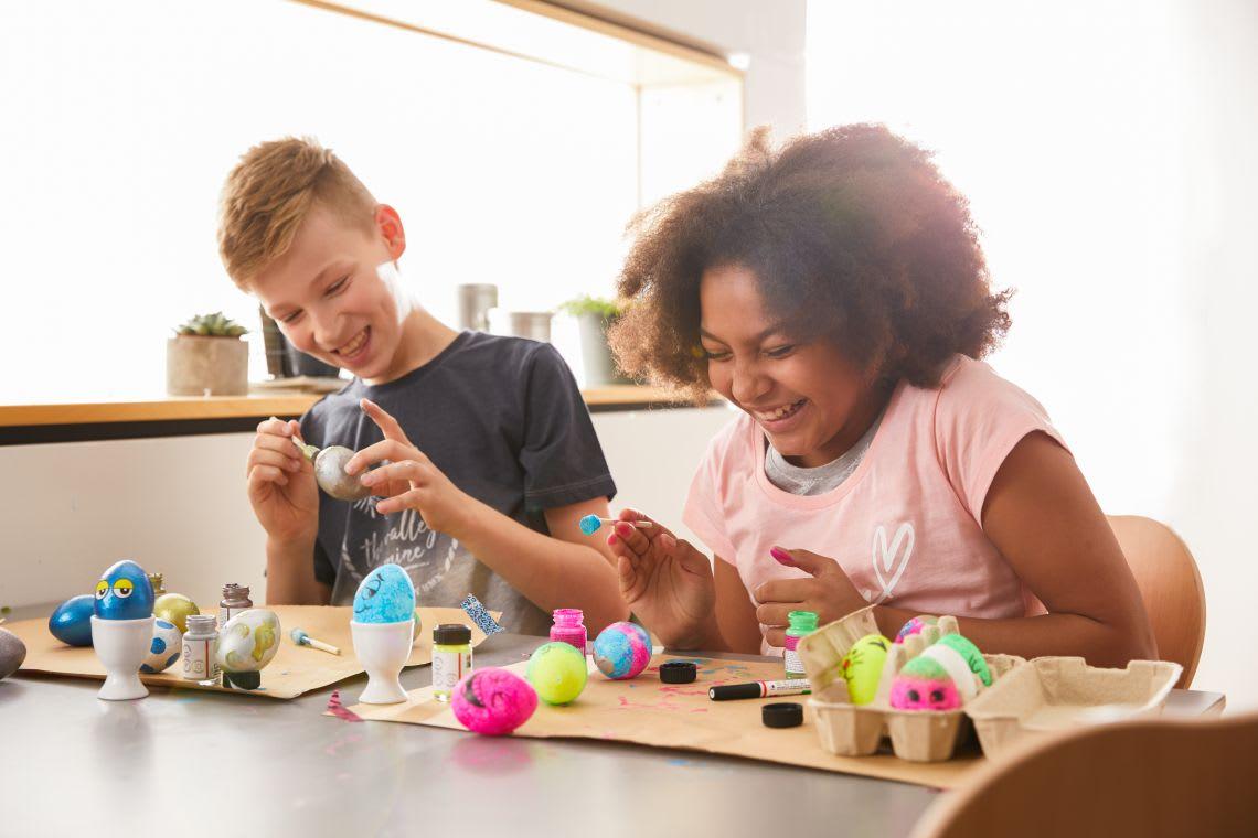 Kinder färben Ostereier am Küchentisch