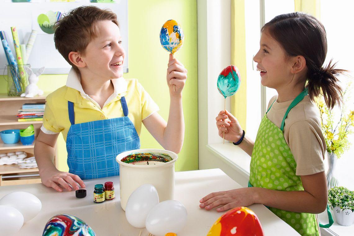 Basteln für Ostern: Kinder färben Ostereier