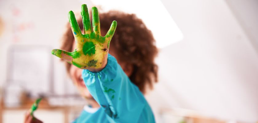 Basteln mit Kleinkindern: Junge mit bunter Hand voller Fingerfarbe