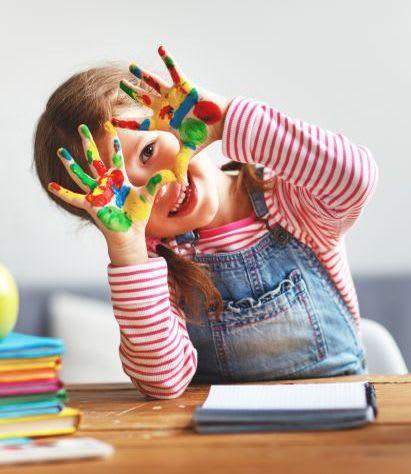 Basteln mit Kleinkindern: Mädchen malt mit Fingerfarben