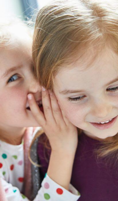Familienspiel-Ideen: Kinder spielen stille Post