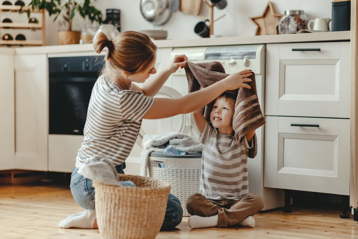 Familienzusammenhalt: Mutter erledigt Hausarbeit mit Kind