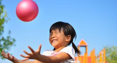 Mädchen spielt Gartenspiel mit Ball