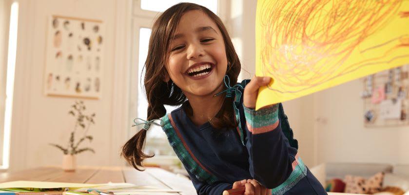 Basteln mit Kindern: Mädchen zeigt gemaltes Bild