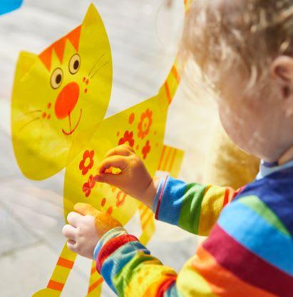 Basteln mit Kindern: Mädchen klebt Fensterbild