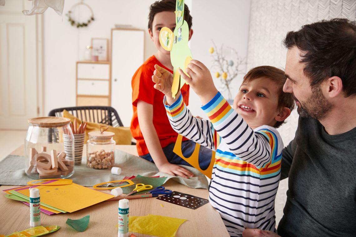 Basteln mit Kindern: Vater mit Söhnen beim Osterbasteln