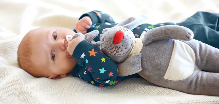Kuscheltiere zum Einschlafen: Baby kuschelt mit Schnullerhasen