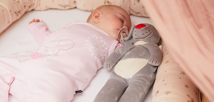 Kuscheltiere zum Einschlafen: Baby liegt im Bettchen mit Schnullerhasen