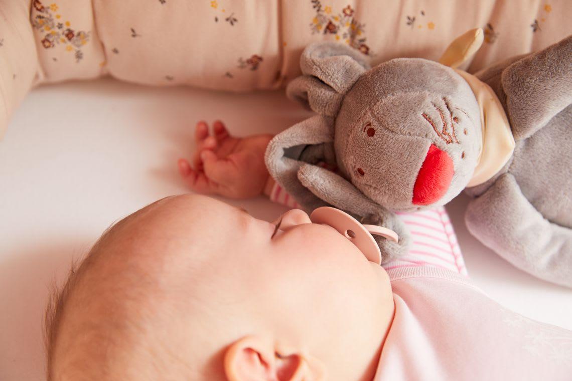 Kuscheltiere zum Einschlafen: Baby schläft im Bettchen mit Schnullerhasen