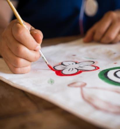 Muttertagsgeschenke basteln: Kind malt Blumen auf Stofftasche