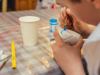 Muttertagsgeschenke basteln: Junge malt Herz auf weiße Tasse