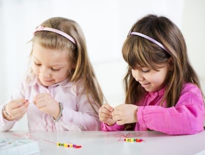 Muttertagsgeschenke basteln: Mädchen basteln gemeinsam Armbänder