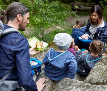 Familie macht beim Wandern ein Picknick mit Kindern