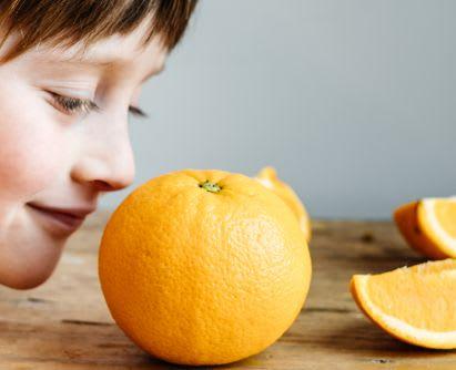 Spiele selber machen: Junge riecht beim Duft-Memory an Orange