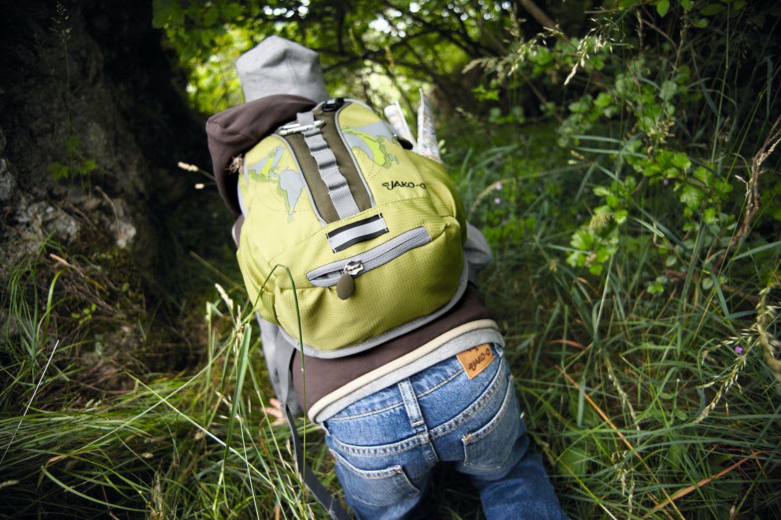 Ausflüge mit Kleinkind: Kind wandert mit Rucksack durch das Gras