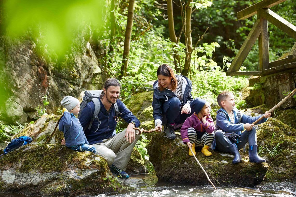 Unternehmungen mit Kindern: Familie sitzt am Fluss