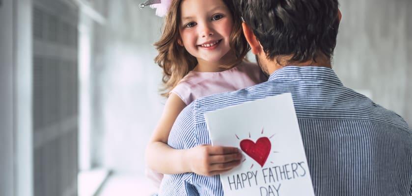 Vatertagsgeschenke basteln: Kind mit gebastelter Karte auf Papas Arm