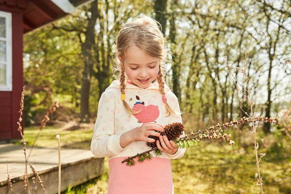 Mädchen sammelt Tannenzapfen zum Basteln