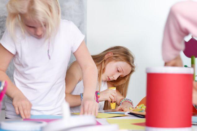 Zwei Mädchen basteln konzentriert eigene Laternen