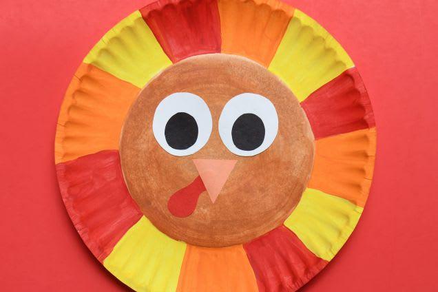 Laternen basteln: Ein Pappteller in bunten Farben stellt den Kopf eines Huhns dar
