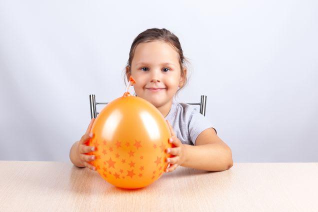 Laternen basteln: Ein Mädchen an einem Tisch hält einen Luftballon fest