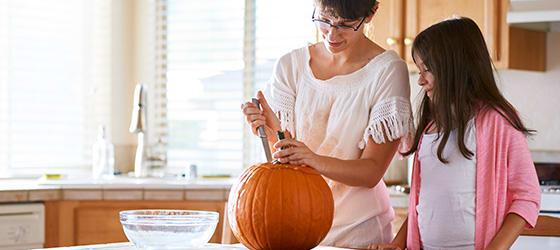 mother_and_daughter_having_fun_carving_pumpkin01.jpg