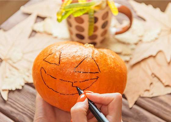 Womans_hands_drawing_a_face_sketch_on_pumpkin_to_Halloween.jpg